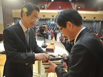 수습전권위원장 채영남 목사가 신임 노회장 김권수 목사에게 성경, 헌법, 의사봉을 전달하고 있다.